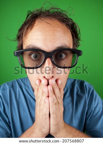 Thirty year old man with 3d glasses in shock watching a movie over a green background - stock photo