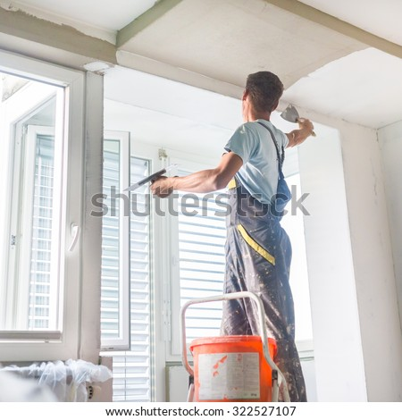 Thirty years old manual worker with wall plastering tools inside a house. Plasterer renovating indoor walls and ceilings with float and plaster. - stock photo