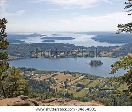 This aerial scenic landscape is a view of Campbell Lake with a small island and the San Juan Islands off of the Washington state coast. - stock photo
