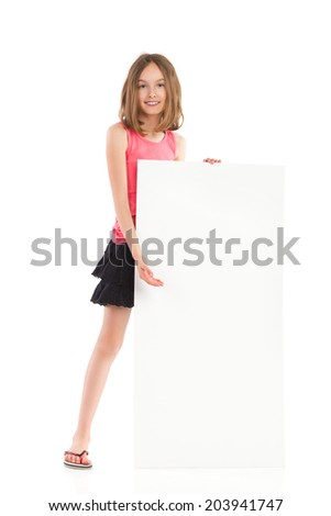 This banner is waiting for your message. Cute little girl standing behind blank banner and pointing. Full length studio shot isolated on white. - stock photo
