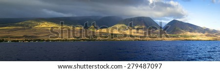 This beautiful sunset view of the West Coast of Maui Hawaii shows the tall mountains, valleys and shield volcano making up one third of this island. This view taken from a sunset dinner cruise. - stock photo