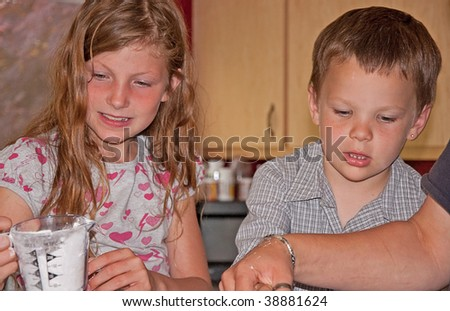 This brother and sister are cooking in the kitchen and enjoying measuring ingredients. - stock photo