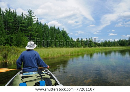 This canoer is heading up the Agnes River in Quetico Provincial Park - stock photo