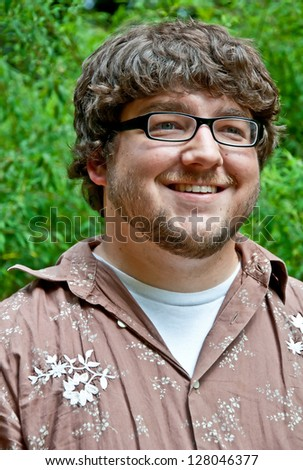 This Caucasian young adult male is in his early twenties in this outdoor portrait.  He's wearing black rimmed glasses and has some facial hair and has a look of a techy, geek or nerd in style. - stock photo