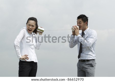 This conceptual image is about communication. Asian Business man and woman using Tin Can Phone. - stock photo