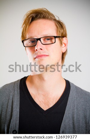 This contemporary style portrait of a man wearing a black shirt and a grey cardigan sweater while wearing glasses in the studio. - stock photo