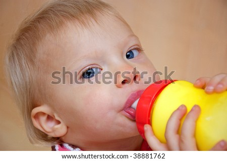This cute blue eyed toddler girl is drinking milk from a brightly colored sippie cup. - stock photo