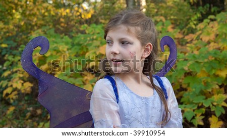 This cute 9 year old girl is wearing a ferry princess costume outdoors against fall leaves in a Halloween outfit. - stock photo