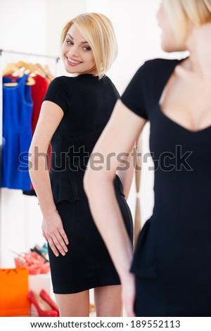This dress is perfect! Beautiful young blond hair woman in black dress looking at the mirror and smiling - stock photo