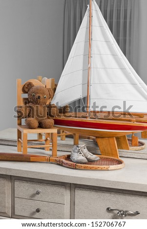 This dresser has some items from childhood through youth that include baby shoes, teddy, and little chair, sailboat, and tennis racket. These kinds of things can quickly trigger cherished memories.  - stock photo