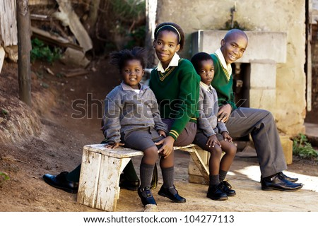 This family of school kids waiting for the bus to their way to school. - stock photo