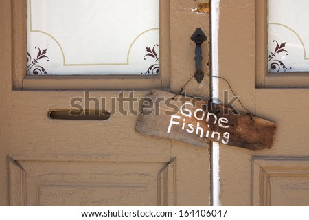 This Gone Fishing sign hanging on the front door of an old country store tells a story of the simple life of a store keeper during a warm rural summer day. - stock photo