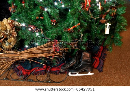 This holiday still life shows black vintage skates under a lit Christmas tree with a bear to the side, wrought iron decor with sticks, homespun and primitive handmade ornaments decorate the tree. - stock photo