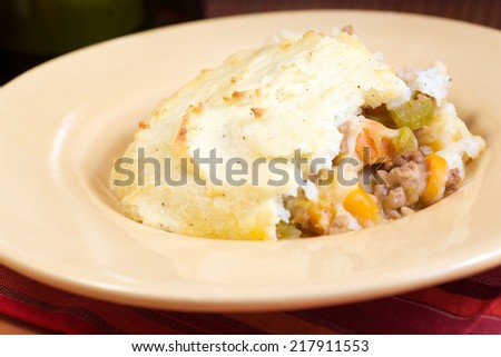 This homemade Shepherd's Pie is made with with fresh vegetables,  ground meat in a savory sauce, topped with mashed potatoes and baked to golden color.  - stock photo