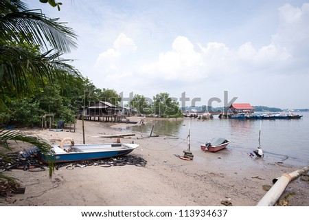 This image shows a Beach and wooden jetty on Pulau Ubin, Singapore - stock photo