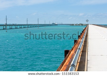 This image shows the original seven mile bridge and the current highway. Pigeon Key is in the background. - stock photo
