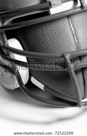 This is a black and white, high contrast shot of an old football helmet with a football inside. - stock photo