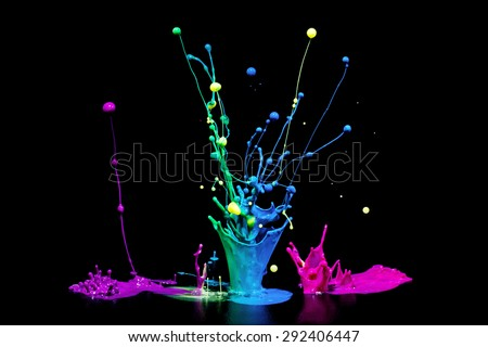 This is a colorful paint splash on a audio speaker isolated on a black background. This shows the color of music. - stock photo