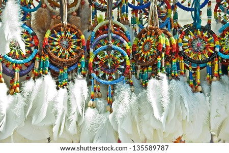 This is a group of Native American beaded dream catchers, with white feathers at the bottom. - stock photo