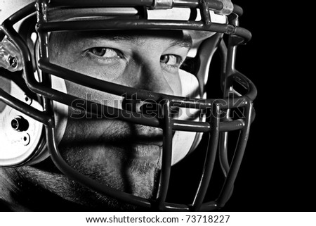 This is a high contrast, black and white image of a young man with an intense look on his face wearing a football helmet. Processed to enhance skin texture. - stock photo
