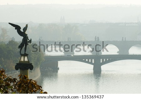 This is a morning view of the bridges on the Vltava River in Prague, Czech Republic. Mythologycal sculpture is in the foreground. - stock photo