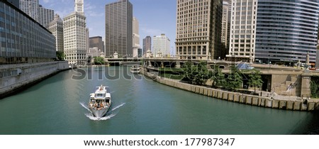 This is a tour boat on the Chicago River during summer. The Chicago Tribune Building, Chicago Sun Times Building, and the IBM Building surround the river. - stock photo