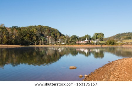 This is a tranquil scene of a lake and small group of buildings along Highway 64 in North Carolina. - stock photo