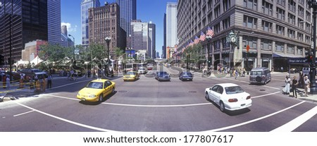 This is a view of State Street with taxis coming in both directions. The historic Marshall Fields Building and clock are on the right.  - stock photo