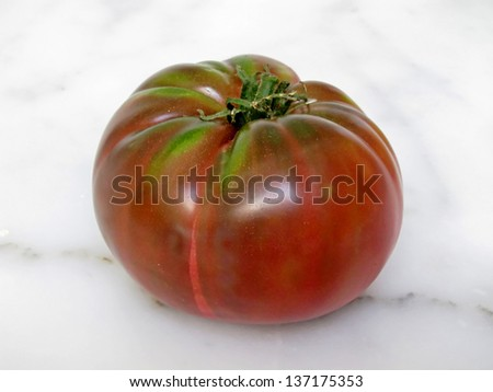 This is a whole, red heirloom tomato sitting on a white marble counter top, just waiting to be cut into. - stock photo