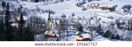 This is an aerial view of a town in Vermont. There is a black steepled church and a small village. The village is covered in snow with houses spread across the field. - stock photo