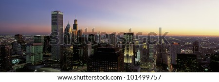 This is an aerial view of the Chicago skyline at sunset. It is a summer evening and the lights of the city are on. - stock photo