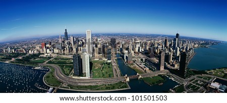 This is an aerial view of the Chicago skyline, Lake Michigan and the Chicago Harbor on left during summer.  Boats are moored in the harbor and Lake Shore Drive winds around the city. - stock photo