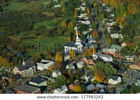 This is an aerial view of the New England village of Stowe. It is along scenic Route 100. There is autumn foliage in the trees. It is a typical looking small New England town. - stock photo