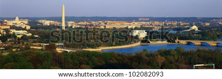 This is an aerial view of Washington, DC. The Potomac River runs through the center with the Key Bridge at right at sunset. - stock photo