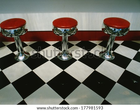 This is an art deco style restaurant. It has a black and white checkerboard tile floor with red vinyl stools next to the counter. It is a typical 50's style diner. - stock photo