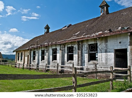 This is an old abandoned dairy farm with a large barn and old wood fence, on a bright sunny day in a horizontal format.  Beautiful country scene. - stock photo