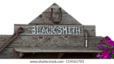 This is an old sign with word blacksmith on rustic wood boards and rusty old vintage tools.  Purple petunia flowers add a splash of color.  Isolated on a white background. - stock photo