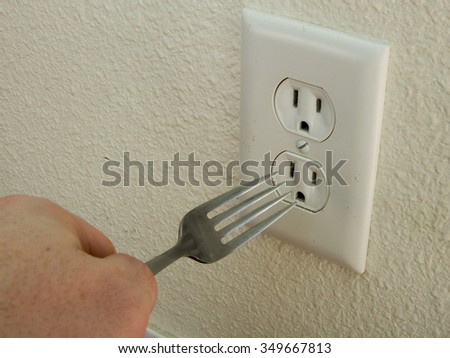 This is dangerous. Do not put metal into a wall outlet - stock photo