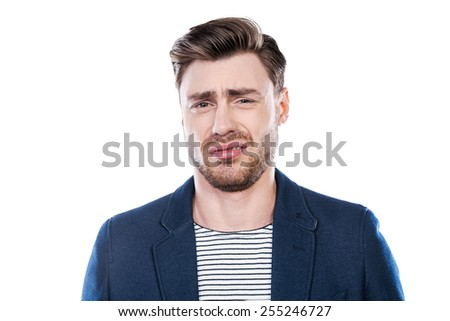 This is disgusting! Portrait of young man expressing negativity and looking at camera while standing against white background - stock photo