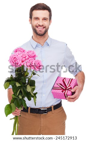 This is for you! Handsome young man holding gift box and stretching out bouquet with pink roses while standing isolated on white background   - stock photo