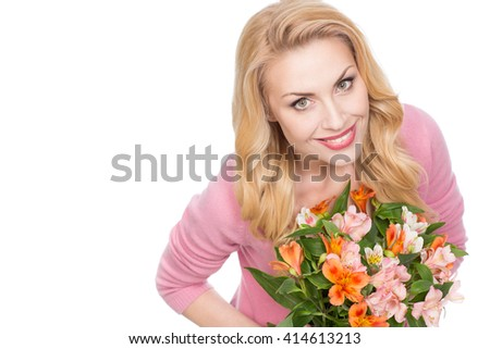 This is her day. Top view of a stunning beautiful mature woman smiling joyfully to the camera holding a bunch of flowers isolated on white - stock photo