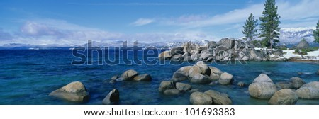This is Lake Tahoe after a winter snow storm. There is a full moon over the lake and snow on the sandy shore. - stock photo