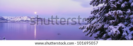 This is Lake Tahoe after a winter snow storm. There is a full moon rising over the lake and the trees and mountains are covered in snow. - stock photo