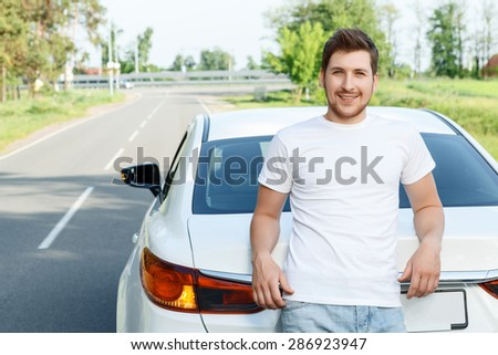 This is mine. Handsome happy young man with beard standing behind his new car. - stock photo
