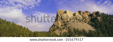 This is Mount Rushmore National Monument set into the mountain showing its natural surroundings against a blue sky. - stock photo