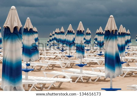 This is the back-end on the beach. Sunshades has been closed, heavy clouds clung to the seaside. - stock photo