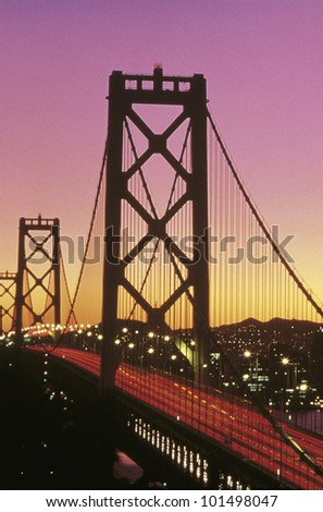 This is the Bay Bridge at sunset. There is a pink and orange glow in the sky. - stock photo