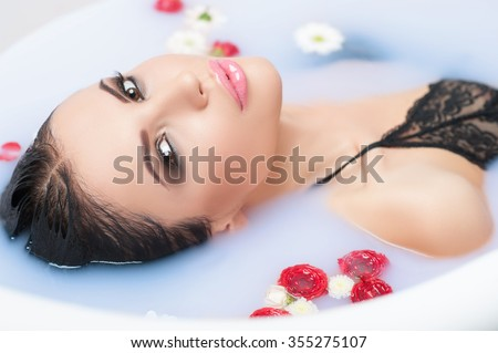This is the best way to relax. Attractive young woman is having a bath with flowers - stock photo