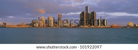 This is the Detroit skyline at sunrise. It shows the Detroit River in the foreground. - stock photo