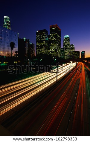 This is the Harbor Freeway with the streaked lights from rush hour traffic at sunset. The skyline is to the left of the freeway. - stock photo